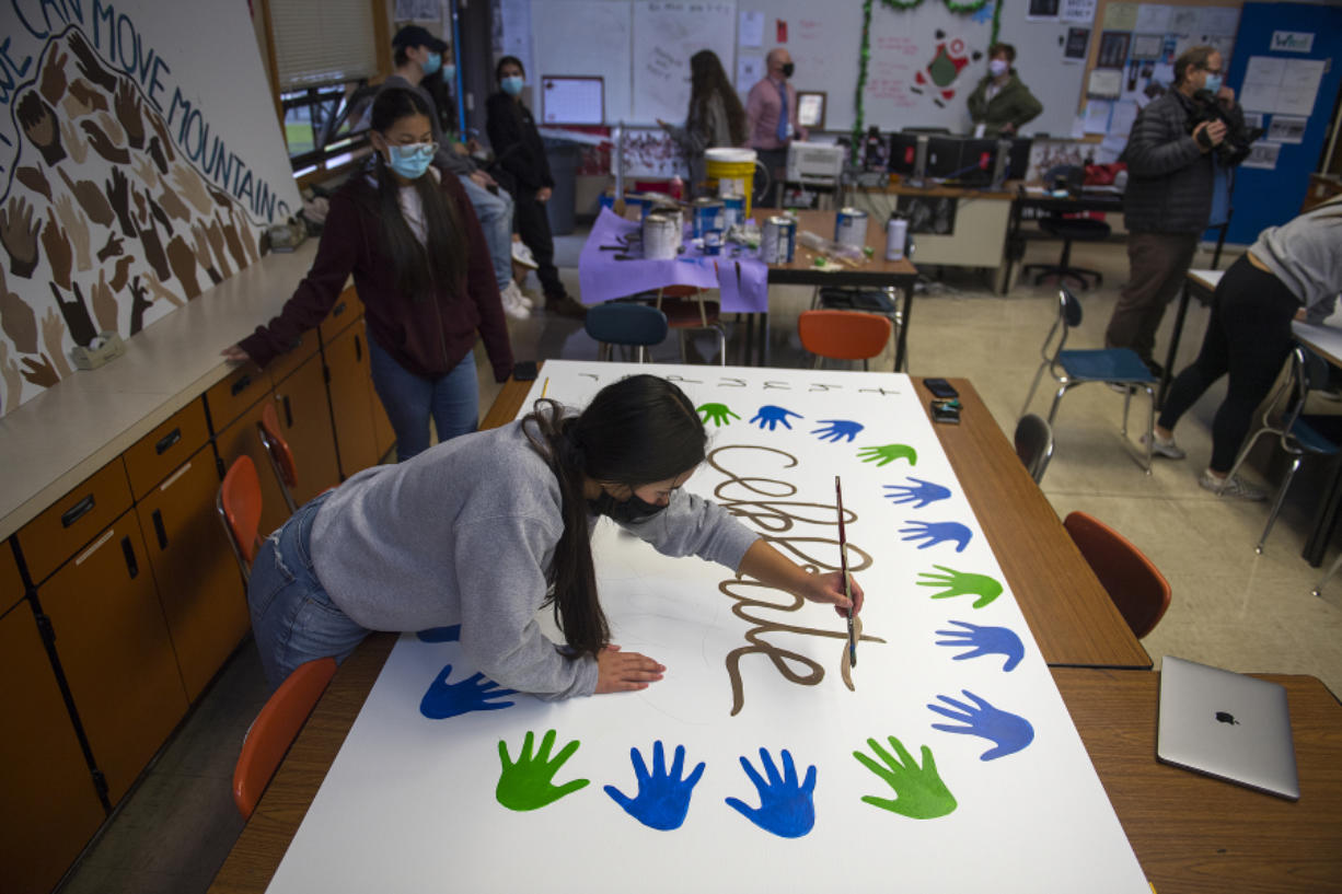 Mountain View High School junior Makaila Inoncilo, 16, foreground, joins fellow leadership student Nancy Flores, 16, also a junior, while creating a mural with a positive message. The murals created by the leadership students will be displayed on campus.