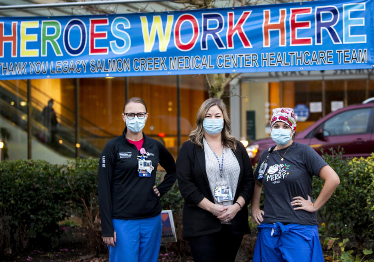 """Melissa Glascock, from left, a respiratory therapist, Colette Reilly, a nurse manager, and Lisa Streissguth-Kasberg, a charge nurse, pose in front of a """"Heroes Work Here"""" banner outside Legacy Salmon Creek Medical Center. Clark County hospitals have seen spikes in coronavirus patients this fall and winter."""