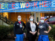 "Melissa Glascock, from left, a respiratory therapist, Colette Reilly, a nurse manager, and Lisa Streissguth-Kasberg, a charge nurse, pose in front of a ""Heroes Work Here"" banner outside Legacy Salmon Creek Medical Center. Clark County hospitals have seen spikes in coronavirus patients this fall and winter."