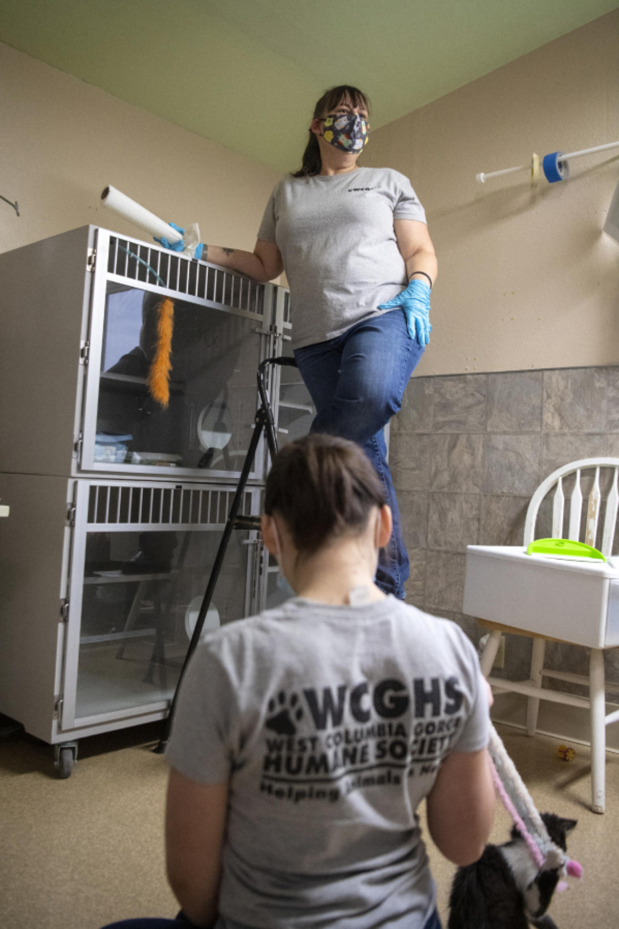Volunteer Pamela Sanseri speaks to a reporter while her daughter, Gabrielle, plays with a cat in the intake room designated for new feline additions to the facility at the West Columbia Gorge Humane Society in Washougal.