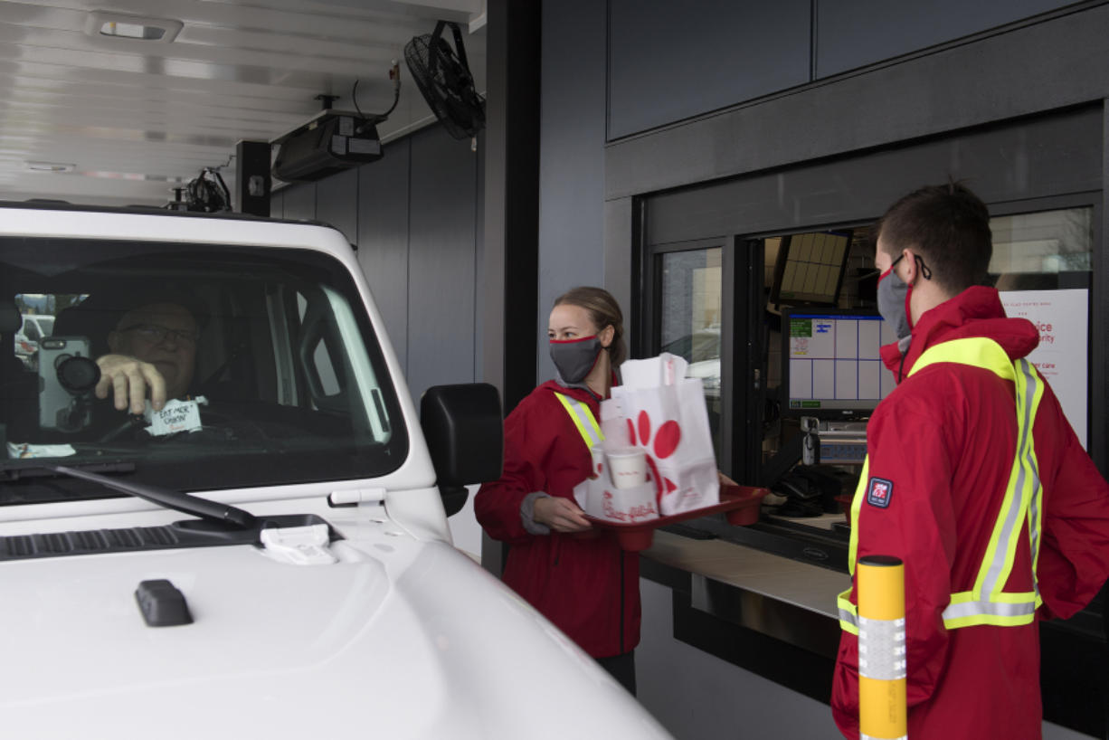 Keith Hallett of Vancouver, from left, who was one the first customers through the drive thru at the new Chick-fil-A restaurant, picks up his order from Tanya Bogdanov as Sawyer McIntosh lends a hand at Vancouver Mall on Thursday morning, January 7, 2021.