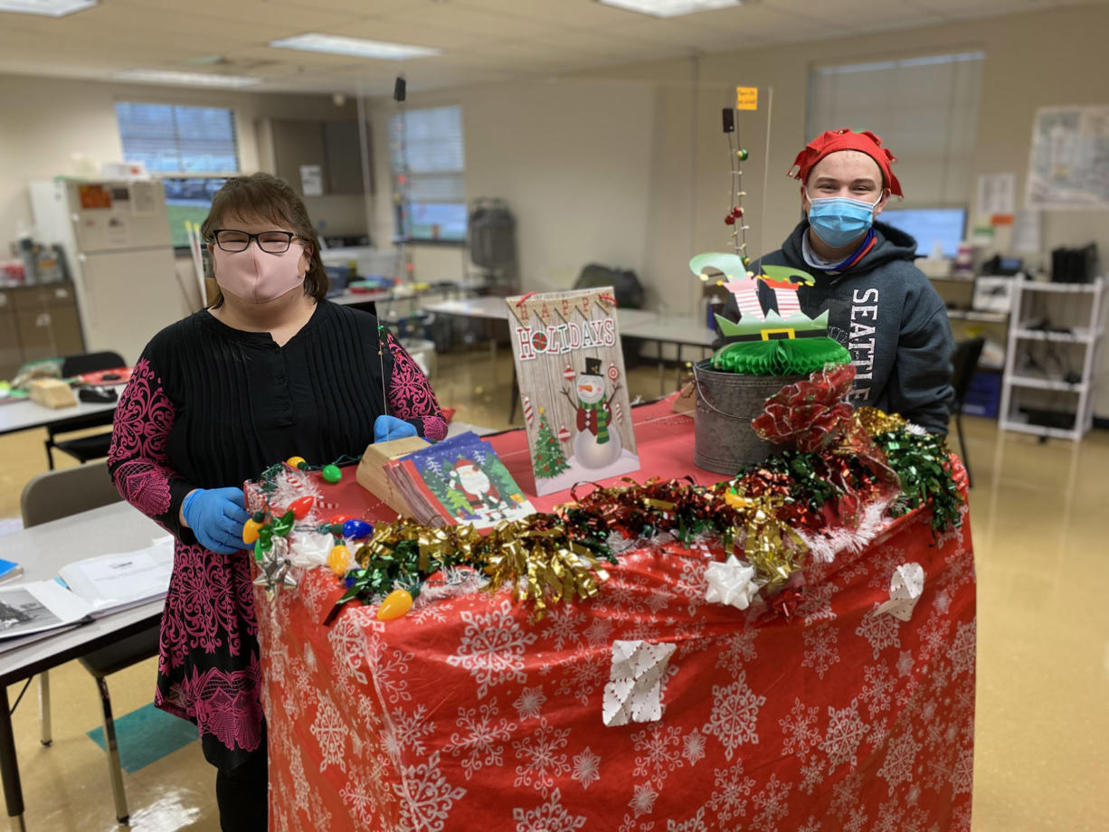 WASHOUGAL: Tiffaney Forney, Washougal Adult Transition Program job coach and Washougal High School freshman Blake Early prepare to roll holiday treats out to teachers.
