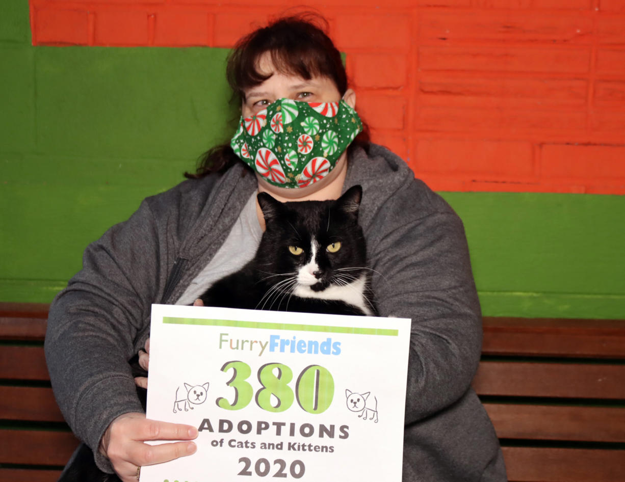 MINNEHAHA: Julie Goldbeck holds cat Milo with a sign marking a historic number of adoptions during 2020 for Furry Friends.