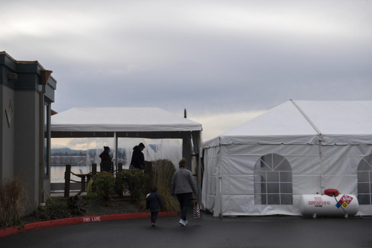 Customers make their way into a dining tent along the exterior of Beaches Restaurant & Bar on Thursday. Indoor dining has been banned in Washington since November due to a spike in COVID-19 cases.