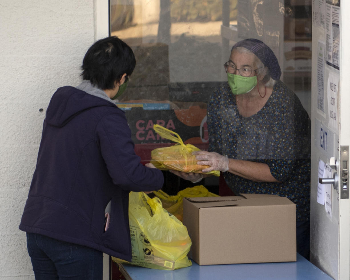 Volunteer Libby Bryant helps a food recipient at FISH Westside Food Pantry of Vancouver. The pantry serves about 1,200 families, or 3,500 people every month, Executive Director James Fitzgerald said.