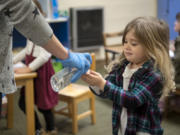 Parent helper Sarah Stowe gives Aurora Lund, 3, a pump of hand sanitizer following snack time on Tuesday at the Camas-Washougal Parent Co-Op preschool. All students received hand sanitizer after snack time before returning to coloring projects.