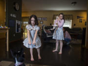Andrea Heldt of Vancouver looks on while her daughter, Nora, 7, bonds with puppy Thea as her other daughter, Kylee, 9, plays the piano Wednesday afternoon. The girls used to be enthusiastic about school, but they have been less engaged as remote learning drags on. The Heldt family tries to have fun together to keep things positive during the pandemic.