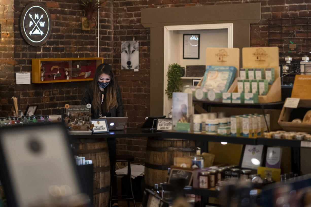 Store owner Jessica Chan works on her laptop Saturday at NMV Pop-Local on West Ninth Street in downtown Vancouver.