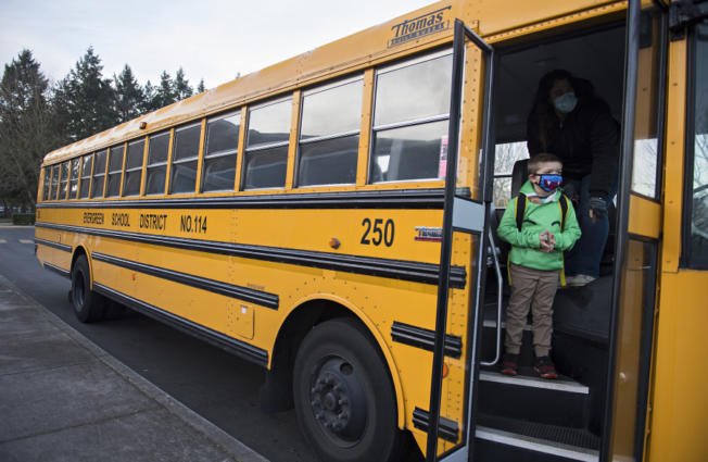 First-grader Kolby Schave, 6, prepares to depart the school bus while arriving for hybrid classes at Crestline Elementary School on Tuesday morning.