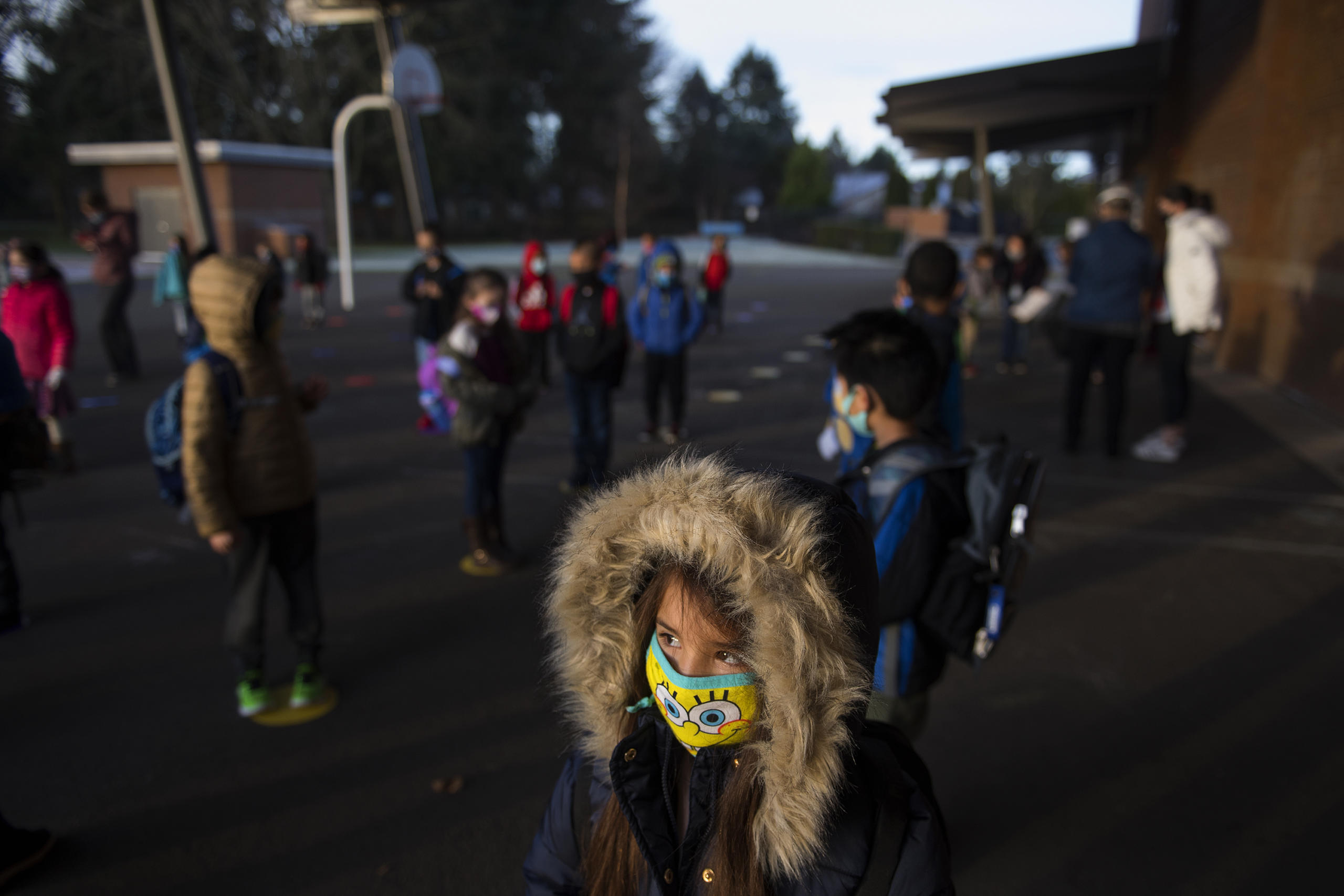 First-grader Mia Pierce, 6, bundles up in a coat before attending hybrid classes at Crestline Elementary School on Tuesday morning, January 19, 2021. More Clark County schools are welcoming students back to the classroom for hybrid learning. (Amanda Cowan/The Columbian)