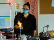 WOODLAND: Stephanie Marshall, a high school science teacher, lights magnesium on fire to demonstrate chemical reactions during a recent virtual science lab.