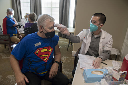 Van Mall Retirement General Manager Bill Hess, left, harnesses his superpowers while getting his COVID-19 vaccination from Jordan Tran of CVS Pharmacy on Friday at Van Mall Retirement. Hess was among the 205 staff and residents that were vaccinated last week. Van Mall had a superhero theme to celebrate staff and residents.