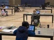 """Students work in the """"Internet Cafe"""" at Captain Strong Primary School in Battle Ground in January. Students are set up with Chromebooks in the gymnasium if they need internet to access remote learning."""
