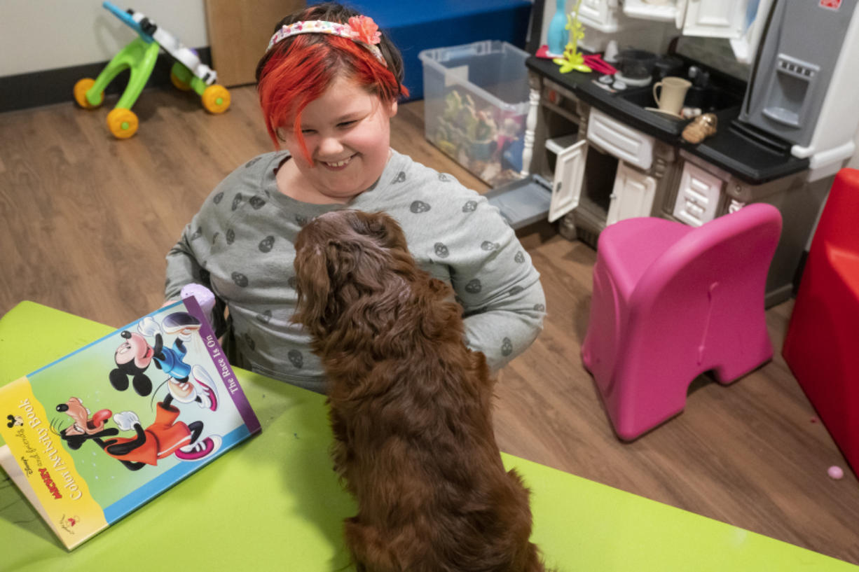 Aurora, the daughter of a resident at the Homestead Share House, and her dog Koda play in a toy room at the newly renovated shelter  on Wednesday afternoon.