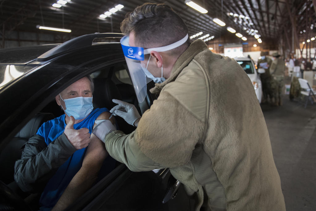 """Chuck Adams of La Center, left, gives a thumbs-up while receiving his COVID-19 vaccination from Staff Sgt. Cory Hoveskeland of the Air National Guard at the Clark County Event Center at the Fairgrounds on Tuesday morning, January 26, 2021. Adams said getting the vaccination went smoothly. """"I didn't even feel it,"""" he said. Tuesday was the first day of mass vaccinations in Clark County, which are given by appointment only."""