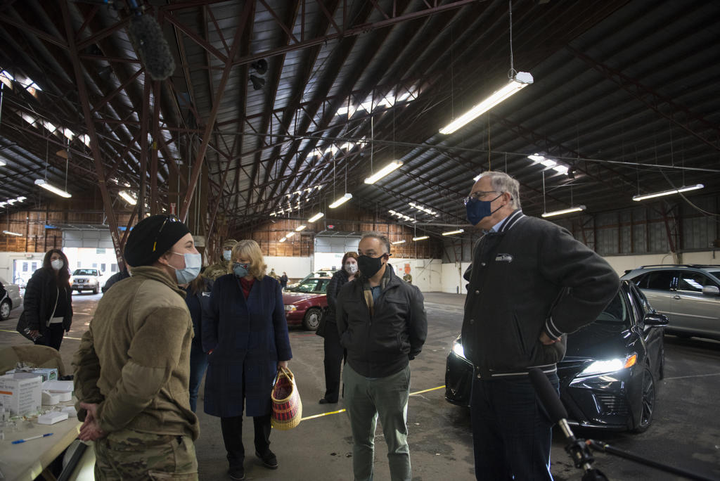 Pvt. Brei Plumb, who is a medic in the Washington National Guard, left, talks with Washington Secretary of Health Dr. Umair Shah, second from right, and Gov. Jay Inslee, right, as they tour the mass vaccination site at the Clark County Fairgrounds on Thursday morning, January 28, 2021.