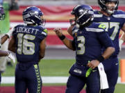 Seattle Seahawks wide receiver Tyler Lockett (16) celebrates his touchdown with quarterback Russell Wilson (3) during the second half of an NFL football game against the San Francisco 49ers, Sunday, Jan. 3, 2021, in Glendale, Ariz. (AP Photo/Ross D.