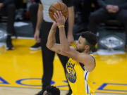 Golden State Warriors guard Stephen Curry (30) takes a three-point shot over Portland Trail Blazers guard CJ McCollum (3) during the first half of an NBA basketball game in San Francisco, Sunday, Jan. 3, 2021.