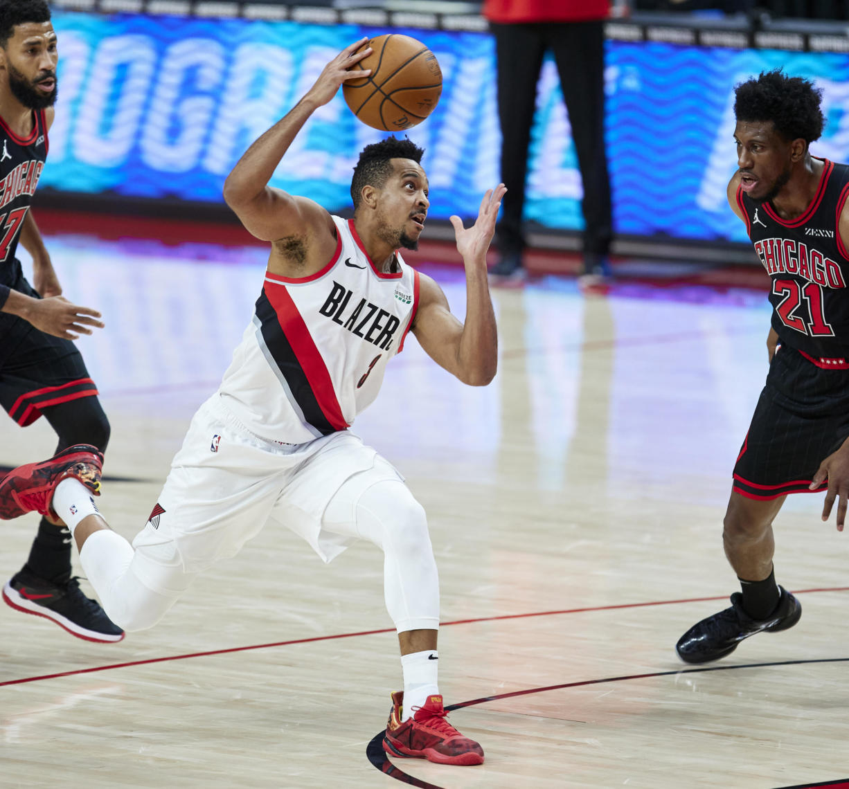 Portland Trail Blazers guard CJ McCollum, center, drives to the basket between Chicago Bulls guard Garrett Temple, left, and forward Thaddeus Young, right, during the first half of an NBA basketball game in Portland, Ore., Tuesday, Jan. 5, 2021.