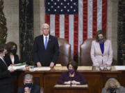Vice President Mike Pence and Speaker of the House Nancy Pelosi, D-Calif., read the final certification of Electoral College votes cast in November's presidential election during a joint session of Congress after working through the night, at the Capitol in Washington, Thursday, Jan. 7, 2021. Violent protesters loyal to President Donald Trump stormed the Capitol Wednesday, disrupting the process. (AP Photo/J.