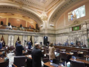 Senate members stand as a ceremonial presentation of colors is done virtually on a video screen above Monday, Jan. 11, 2021, at the Capitol in Olympia, Wash. Washington state's Legislature convened Monday under a large security presence because of concerns about efforts by armed groups who might try to disrupt the proceedings or occupy the Capitol, which is closed to the public due to the ongoing pandemic. (AP Photo/Ted S.