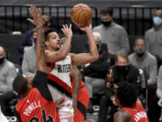 Portland Trail Blazers guard CJ McCollum, center, drives to the basket on Toronto Raptors guard Norman Powell, left, and forward OG Anunoby, right, during the second half of an NBA basketball game in Portland, Ore., Monday, Jan. 11, 2021. The Blazers won 112-111.