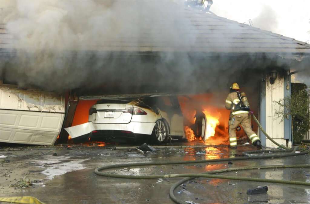 This undated photo provided by National Transportation Safety Board, The Orange County Fire Authority battles a fire on a burning vehicle inside a garage in Orange County, Calif.  When firefighters removed the SUV from the garage to assess the fire , they identified the fuel source as the SUV's high-voltage battery pack.  U.S. safety investigators say electric vehicle fires pose risks to first responders, and manufacturers have inadequate guidelines to keep them safe.