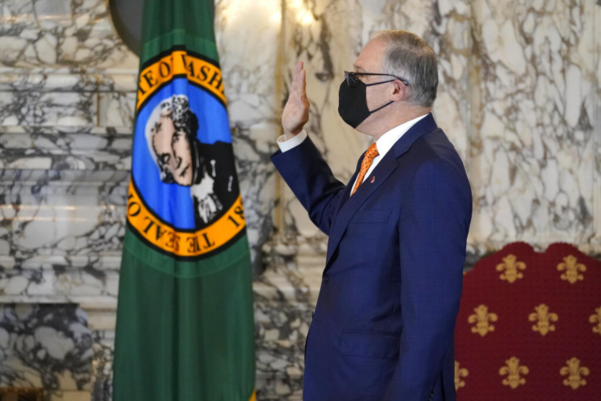 Washington Gov. Jay Inslee takes the oath of office for his third term as Governor, Wednesday, Jan. 13, 2021, during a ceremony at the Capitol in Olympia, Wash. (AP Photo/Ted S.