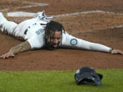 Seattle Mariners shortstop J.P. Crawford sprawls on the dirt and reacts after sliding safely home during the fifth inning of a baseball game against the Houston Astros, Wednesday, Sept. 23, 2020, in Seattle. Crawford scored on a double hit by Kyle Seager. (AP Photo/Ted S.