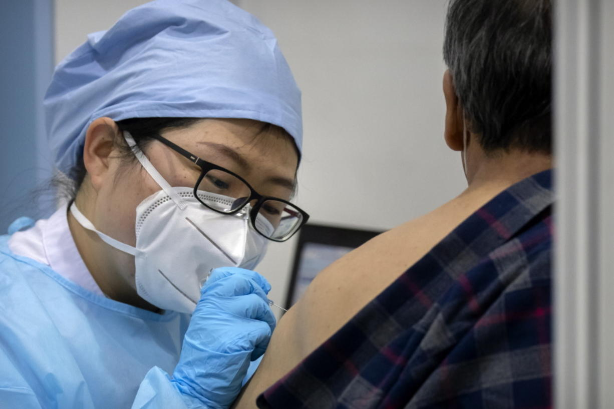 A medical worker gives a coronavirus vaccine shot to a patient at a vaccination facility in Beijing, Friday, Jan. 15, 2021. A city in northern China is building a 3,000-unit quarantine facility to deal with an anticipated overflow of patients as COVID-19 cases rise ahead of the Lunar New Year travel rush.