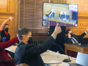"""Members of the Kansas House Federal and State Affairs Committee signal whether they want to be recorded as voting yes or voting no on a proposed anti-abortion amendment to the state constitution, Thursday, Jan. 21, 2021, at the Statehouse in Topeka, Kan. The committee has approved the measure, which would overturn a 2019 Kansas Supreme Court decision declaring access to abortion a """"fundamental"""" right."""