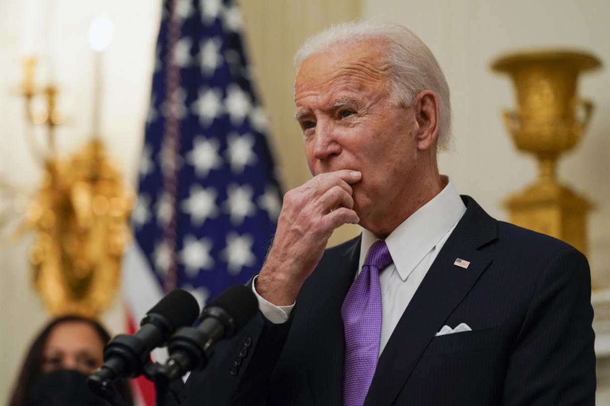 President Joe Biden pauses as he speaks about the coronavirus, accompanied by Vice President Kamala Harris, in the State Dinning Room of the White House, Thursday, Jan. 21, 2021, in Washington.