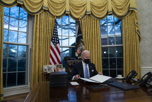 FILE - In this Jan. 20, 2021, file photo President Joe Biden signs a series of executive orders in the Oval Office of the White House in Washington.