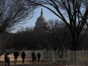 People stroll past a section of the National Mall by the Capitol where workers were still dismantling inauguration installations, after most downtown streets and public spaces had reopened to the public, on Saturday, Jan. 23, 2021 in Washington. Biden is looking to jump-start his first 100 days in office with action and symbolism to reassure a divided and weary public that help is in the offing.