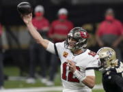 Tampa Bay Buccaneers quarterback Tom Brady (12) works against the New Orleans Saints during the first half of an NFL divisional round playoff football game, Sunday, Jan. 17, 2021, in New Orleans.