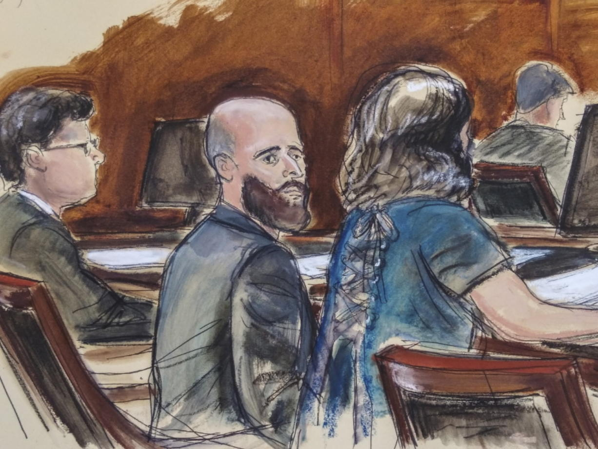 """In this Wednesday March 4, 2020 courtroom sketch Joshua Schulte, center, is seated at the defense table flanked by his attorneys during jury deliberations in New York. Joshua Schulte, a former CIA software engineer charged with leaking government secrets to WikiLeaks says it's cruel and unusual punishment that he's awaiting trial in solitary confinement, housed in a vermin-infested cell of a jail unit where inmates are treated like """"caged animals."""" In court papers Tuesday, Jan."""