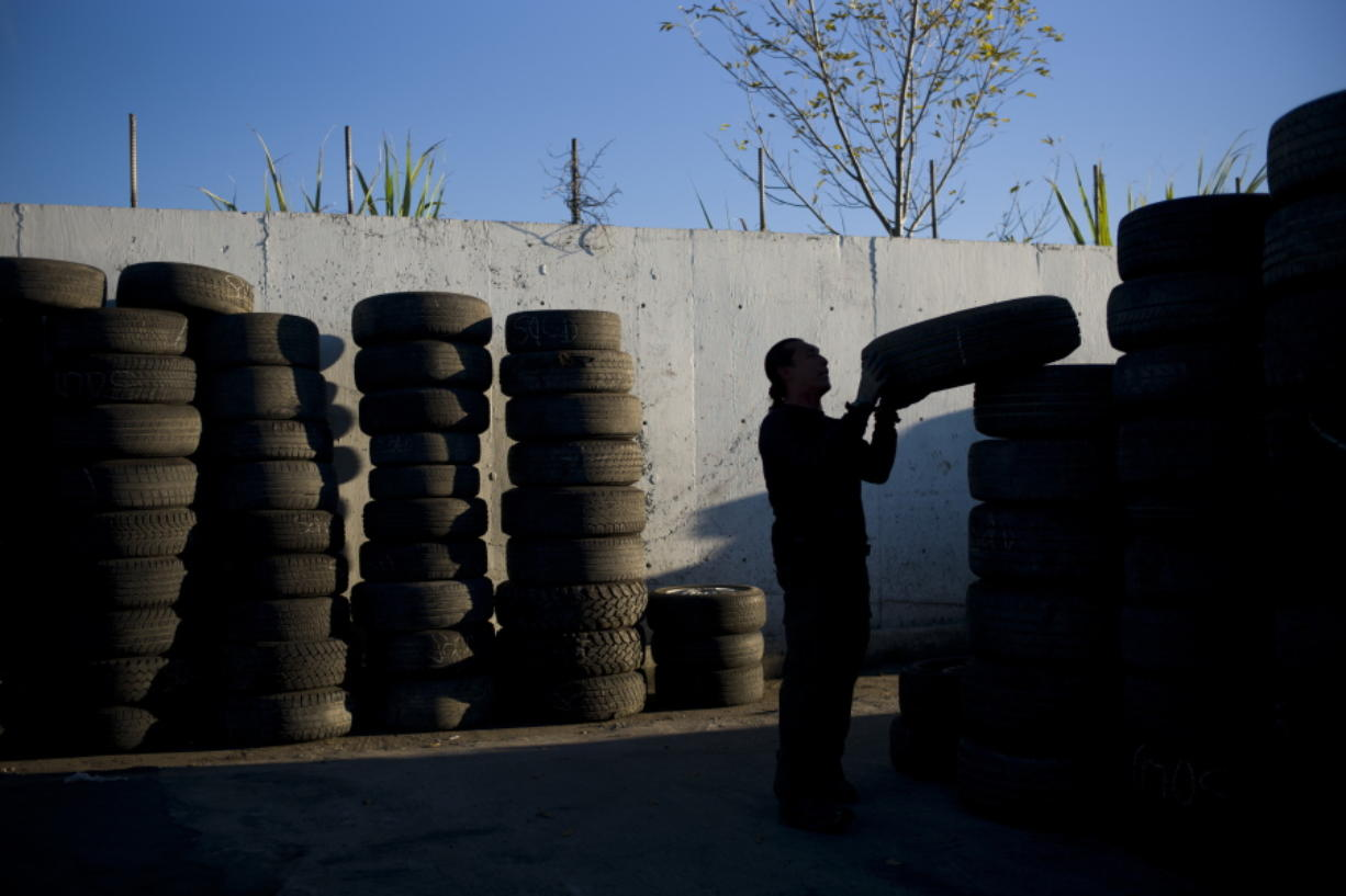 FILE- In this Thursday, Nov. 19, 2015, file photo, junkyard employee Fabio Flores stacks up used tires at Aadlen Brothers Auto Wrecking, also known as U Pick Parts, in the Sun Valley section of Los Angeles. California may ask tire manufacturers to look at ways of eliminating zinc from their products because studies have shown the mineral may harm aquatic wildlife when it is washed into rivers and lakes. (AP Photo/Jae C.