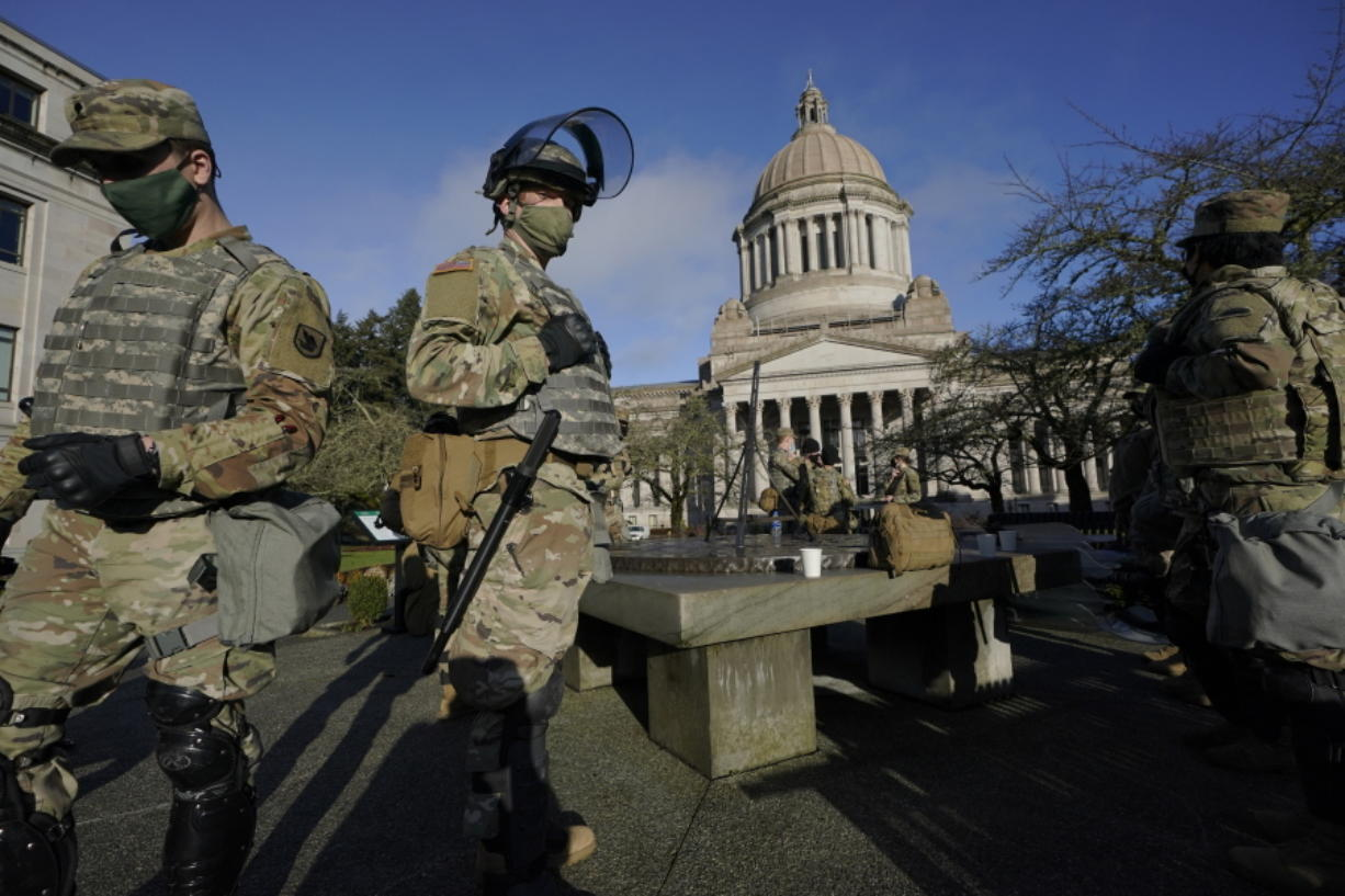 Members of the Washington National Guard stand at a sundial near the Legislative Building, Sunday, Jan. 10, 2021, at the Capitol in Olympia, Wash. Governors in some states have called out the National Guard, declared states of emergency and closed their capitols over concerns about potentially violent protests. Though details remain murky, demonstrations are expected at state capitols beginning Sunday and leading up to President-elect Joe Biden's inauguration on Wednesday. (AP Photo/Ted S.