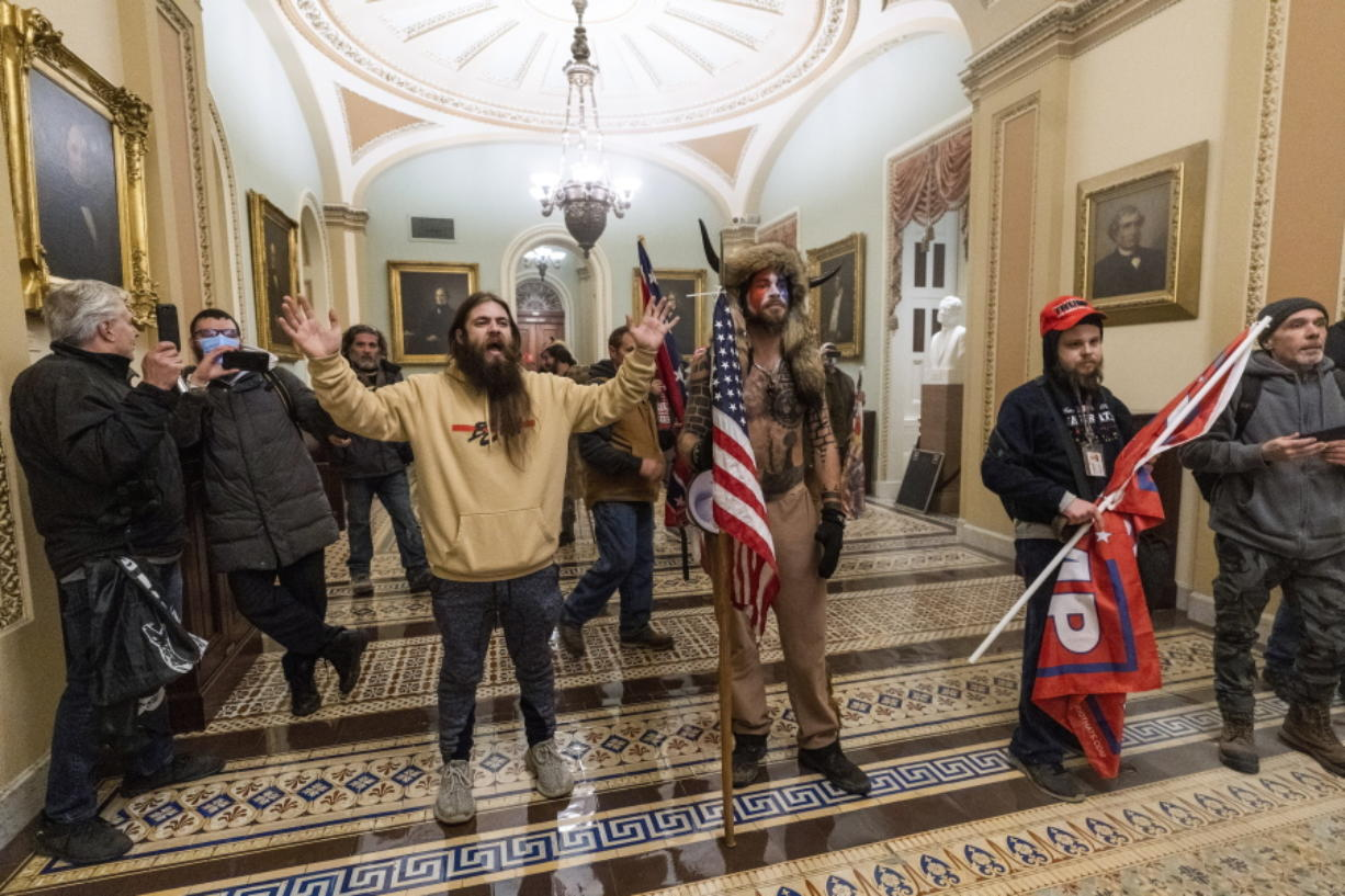 FILE - In this Wednesday, Jan. 6, 2021 file photo supporters of President Donald Trump are confronted by U.S. Capitol Police officers outside the Senate Chamber inside the Capitol in Washington. Jacob Anthony Chansley, the Arizona man with the painted face and wearing a horned, fur hat, was taken into custody Saturday, Jan. 9, 2021 and charged with counts that include violent entry and disorderly conduct on Capitol grounds.