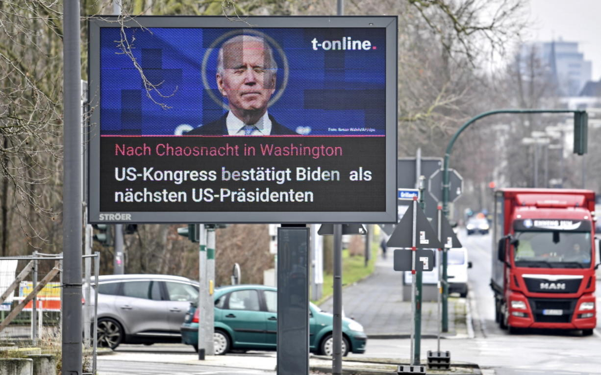 FILE - In this Jan. 7, 2021, file photo, a news screen in Essen, Germany, displays an image of Joe Biden, and a headline reading 'After chaos night in Washington, US Congress confirms Biden as next US President. For America's allies and rivals alike, the chaos unfolding during Donald Trump's final days as president is the logical result of four years of global instability brought on by the man who promised to change the way the world viewed the United States. By seeking to overturn his loss to Joe Biden, Trump upended the bedrock principle of democratic elections that the United States has sought to export around the world.
