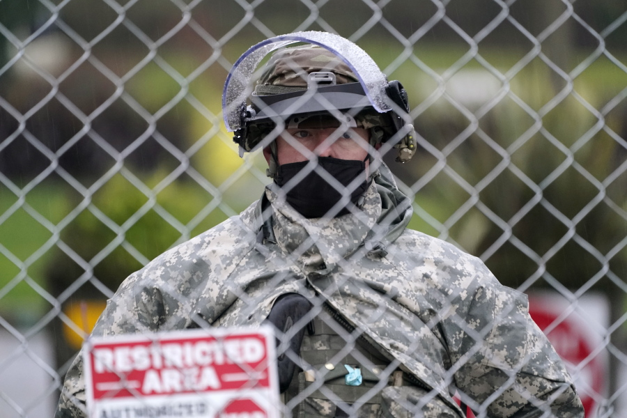 A member of the Washington National Guard stands at a fence surrounding the Capitol in anticipation of protests Monday, Jan. 11, 2021, in Olympia, Wash. State capitols across the country are under heightened security after the siege of the U.S. Capitol last week. (AP Photo/Ted S.