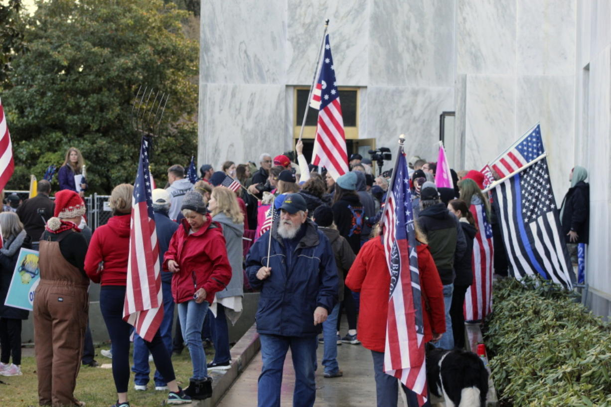 FILE - In this Dec. 21, 2020, file photo, pro-Trump and anti-mask demonstrators hold a rally outside the Oregon State Capitol as legislators meet for an emergency session in Salem, Ore. During the protest Republican lawmaker, Rep. Mike Nearman, physically opened the Capitol's door -- letting protesters, who clashed with police, gain access to the building. There have been calls for Nearman to resign ahead of the upcoming 2021 Legislative session that begins Tuesday, Jan. 19, 2021.