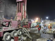 In this photo released by China's Xinhua News Agency, rescuers drill a new channel at the explosion site of a gold mine in Qixia City, east China's Shandong Province, Monday, Jan. 18, 2021. Chinese state media say 12 out of 22 workers trapped for a week by an explosion in the gold mine are alive, as hundreds of rescuers seek to bring them to safety.