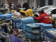 A food delivery worker wearing a face mask to help curb the spread of the coronavirus prepares to deliver foods for his customers outside a restaurant in Beijing on Thursday, Jan. 14, 2021. The e-commerce workers and delivery people who kept China fed during the pandemic, making their billionaire bosses even richer, are so unhappy with their pay and treatment that one just set himself on fire in protest.