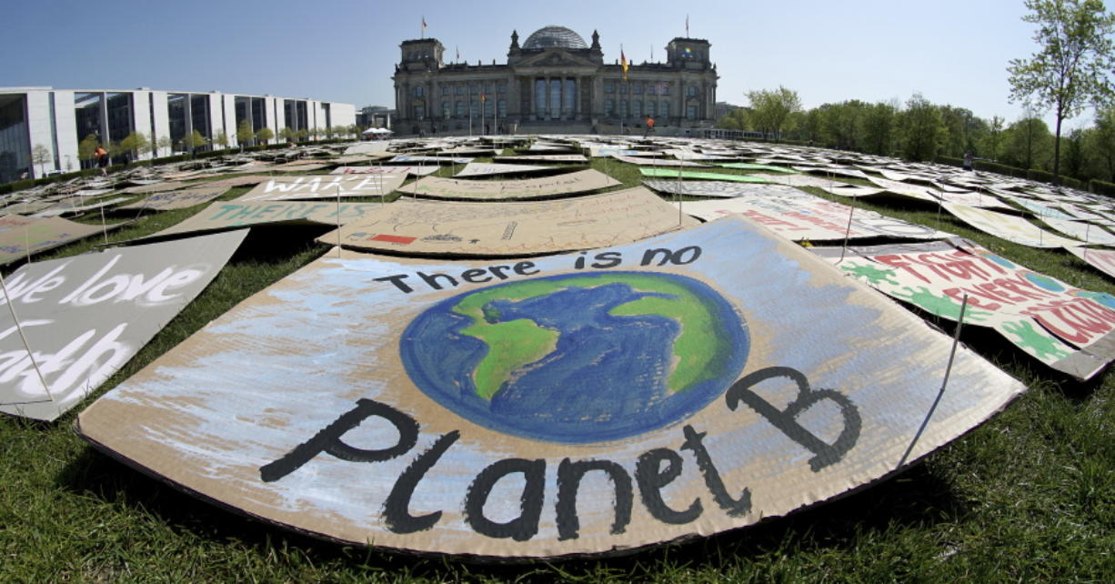 In this Friday, April 24, 2020 file photo, activists place thousands of protest placards in front of the Reichstag building, home of the german federal parliament, Bundestag, during a protest rally of the 'Fridays for Future' movement in Berlin, Germany. World leaders breathed an audible sigh of relief that the United States under President Joe Biden is rejoining the global effort to curb climate change, a cause that his predecessor had shunned.