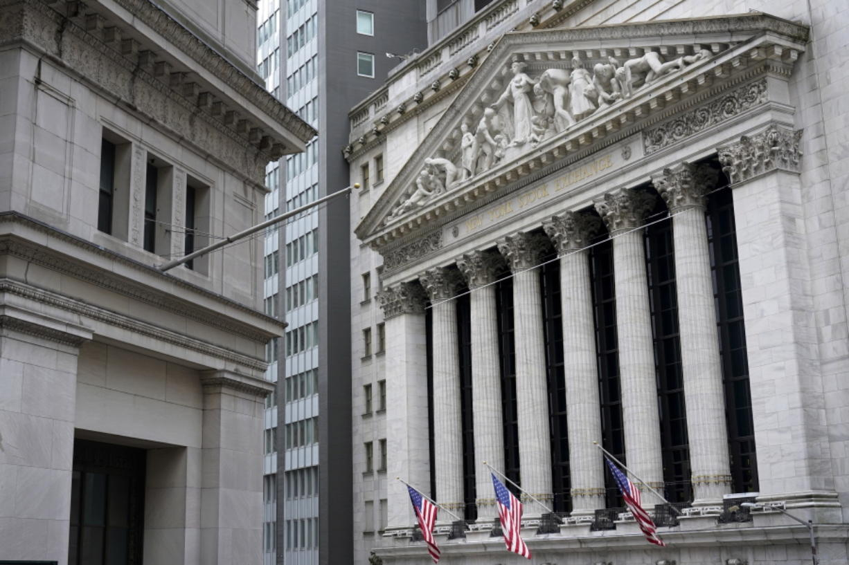FILE - This Monday, Nov. 23, 2020 file photo shows the New York Stock Exchange, right, in New York.  U.S. stocks are ticking higher Thursday, Jan. 14, 2021, despite a dismal report on the number of layoffs sweeping the country.