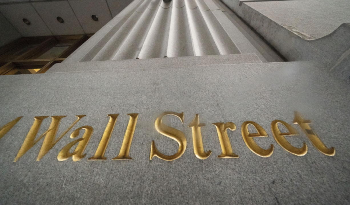 FILE - In this Nov. 5, 2020 file photo, a sign for Wall Street is carved in the side of a building, in New York. Technology stocks were off to a good start on Wall Street, but other parts of the markets weren't as strong, leaving major indexes mixed in the early going. The S&P 500 was up 0.3% in the first few minutes of trading Monday, Jan. 25, 2021, and the tech-heavy Nasdaq climbed 1.4%.