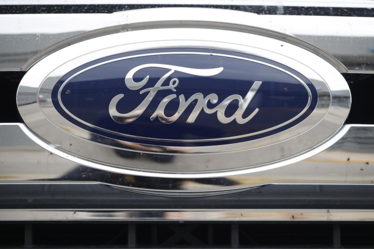 FILE - In this Oct. 20, 2019, file photograph, the company logo shines off the grille of an unsold 2019 F-250 pickup truck at a Ford dealership in Littleton, Colo. Ford Motor Co. posted a stronger-than-expected third-quarter net profit, the company announced Wednesday, Oct. 28, 2020, as demand for cars and trucks recovered from coronavirus shutdowns and the company sold more high-margin trucks.