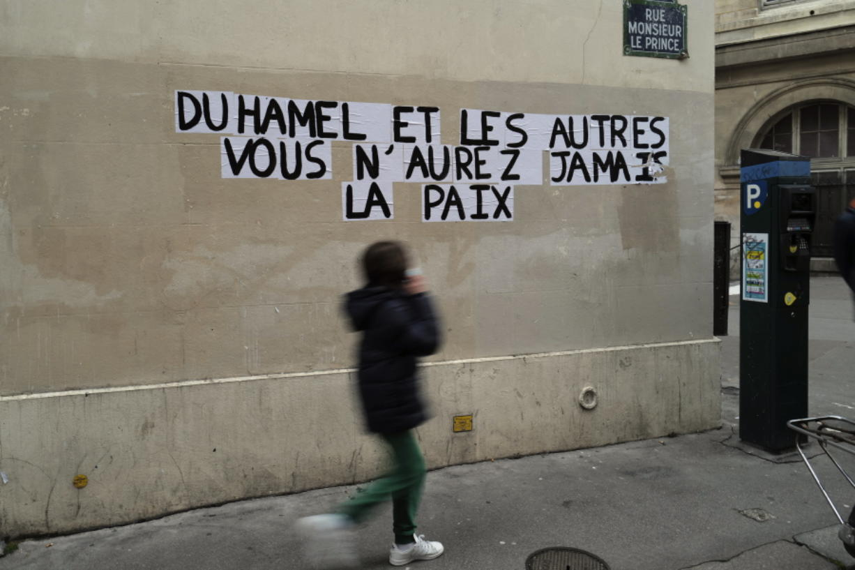 """Signs on the wall reads """"Duhamel, and the others, you will never be in peace"""" referring to prominent French political expert, Olivier Duhamel, in Paris, Tuesday, Jan. 19, 2021. The French government pledged on Thursday to toughen laws on the rape of children, as a massive online movement has seen hundreds of victims share accounts about sexual abuses within their families under the hashtag #MeTooInceste."""
