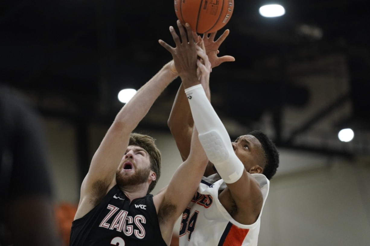 Gonzaga forward Drew Timme, left, and Pepperdine center Victor Ohia Obioha (34) reach for a rebound during the first half of an NCAA college basketball game Saturday, Jan. 30, 2021, in Malibu, Calif.